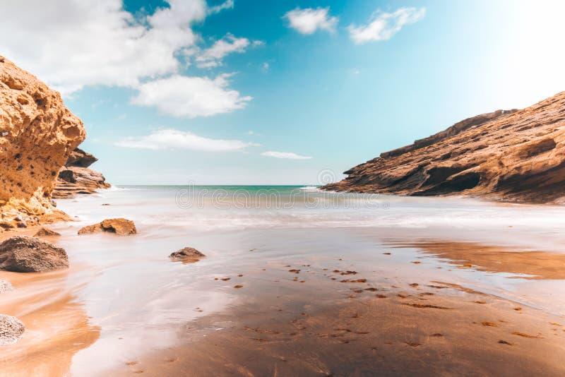 Abandone a praia com rochas e o céu azul do espaço livre fotos de stock