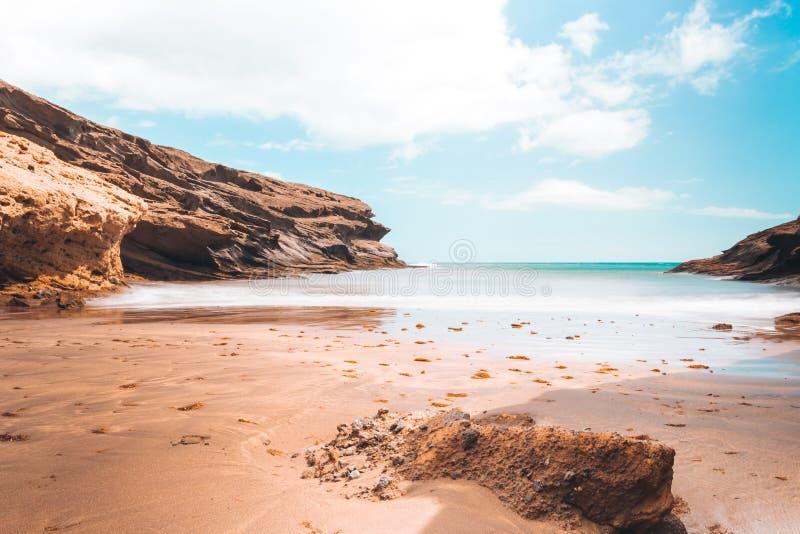 Abandone a praia com rochas e o céu azul do espaço livre foto de stock royalty free