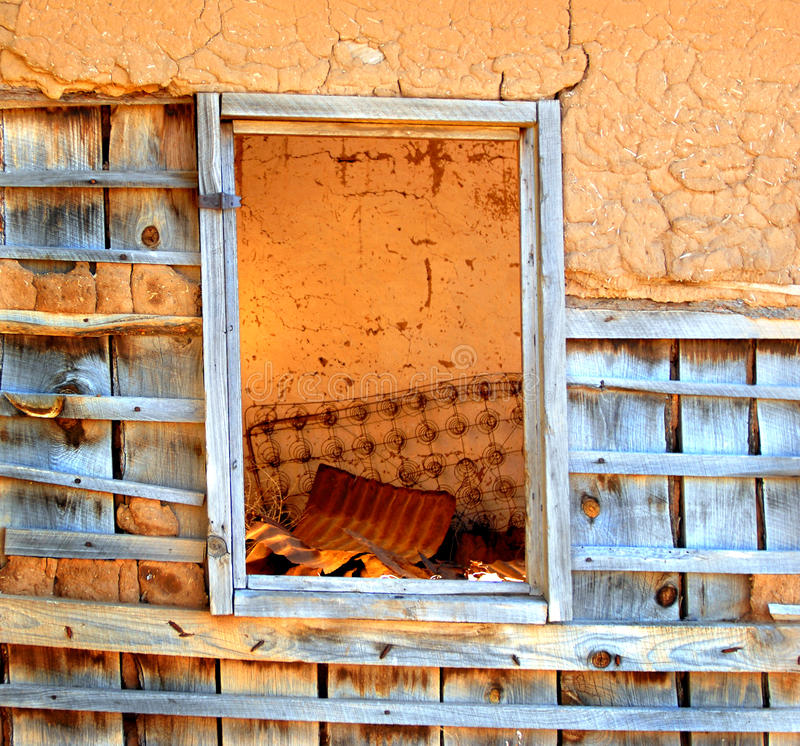 Abandoned Adobe. Window view shows inside of adobe home that has been abandoned. Old rusty bed springs lean against bare wall inside royalty free stock photos