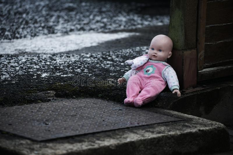 Abandoned baby doll on the street. Low key royalty free stock photo