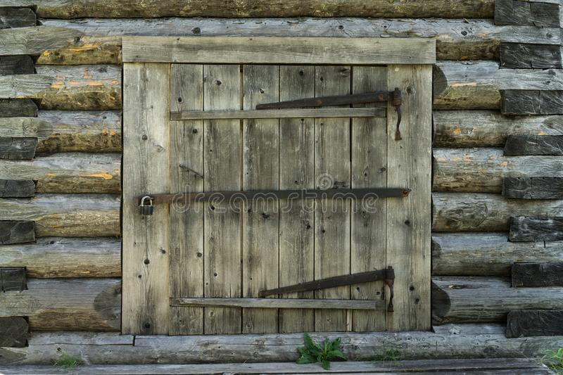 Abandoned barn vintage wooden door. Old photo of rustic house entrance. Abandoned barn antique wooden door. Old photo of the entrance to the village house. Log royalty free stock images