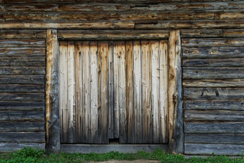 Abandoned barn vintage wooden door. Old photo of rustic house entrance. Abandoned barn antique wooden door. Old photo of the entrance to the village house. Log royalty free stock photos