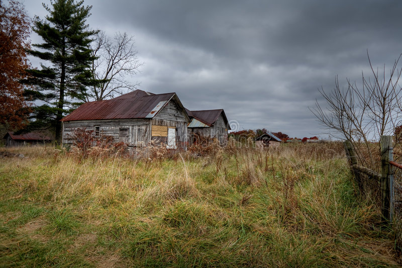Abandoned Barn Under Storm Clouds. Old deteriorated barn out in the country with dark moody clouds overhead stock image