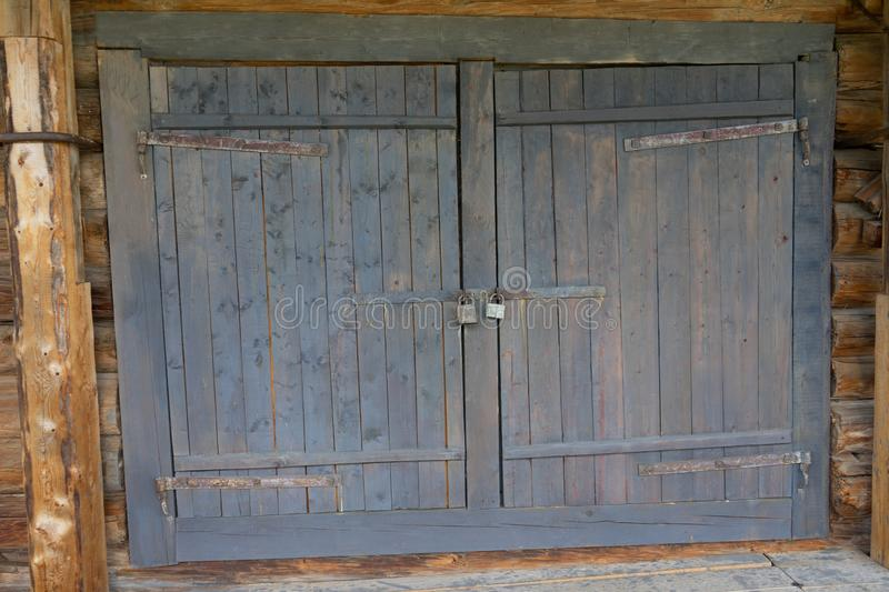 Abandoned barn vintage wooden door. Old photo of rustic house entrance. Abandoned barn antique wooden door. Old photo of the entrance to the village house. Log stock photography