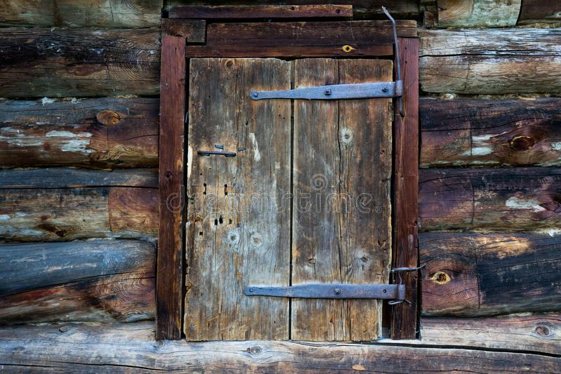 Abandoned barn vintage wooden door. Old photo of rustic house entrance. Abandoned barn antique wooden door. Old photo of the entrance to the village house. Log royalty free stock photo