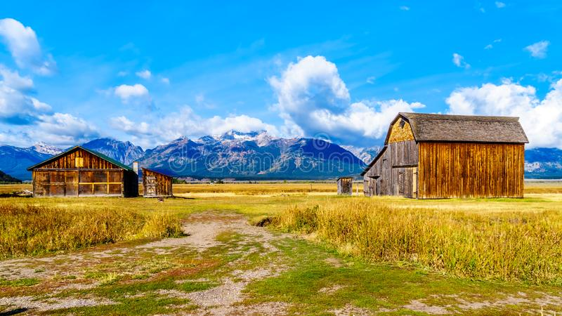 Abandoned Barns at Mormon Row with in the background cloud covered Peaks of the Grand Tetons In Grand Tetons National Park. An abandoned Barns at Mormon Row with stock photography
