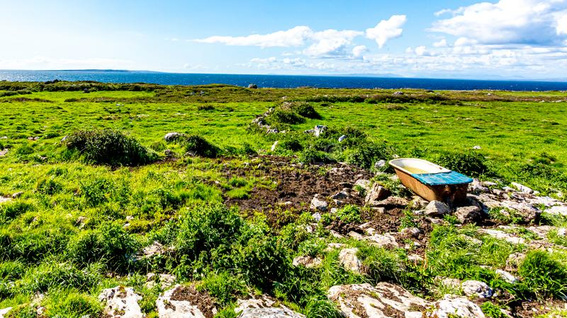 Abandoned bathtub on stones in the Burren with the sea in the background stock photography