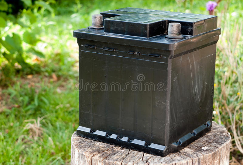Abandoned battery. Dumped. Old battery on tree stump in natural setting. Not recycling royalty free stock photography