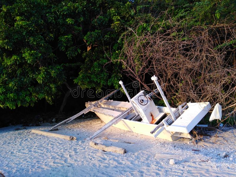 An Abandoned Beached Boat on Tropical White Sands royalty free stock photography