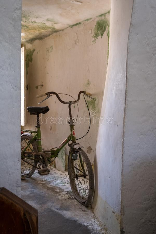 Abandoned bicycle inside a neglected conical roofed Trulli house in Alberobello, Puglia italy. stock photo