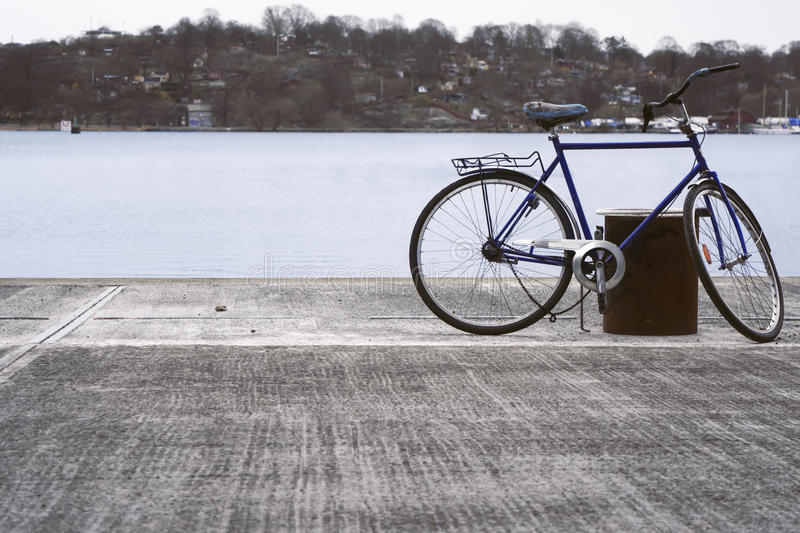 Abandoned bicycle by the water. Broken bicycle left on the pier by the water stock image