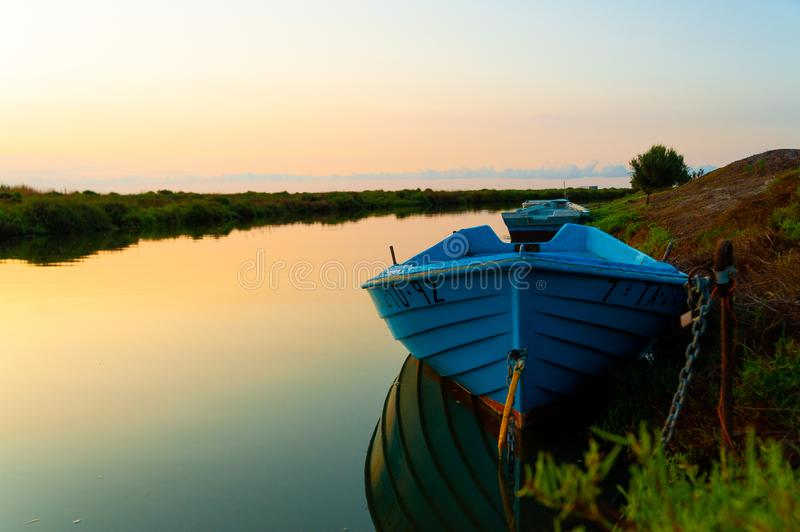 Abandoned blue fishing boat at dawn in ebro delta park in catalunya, a quiet scene with warm colors symbol of loneliness and peace. Blue fishing boat at dawn in stock image