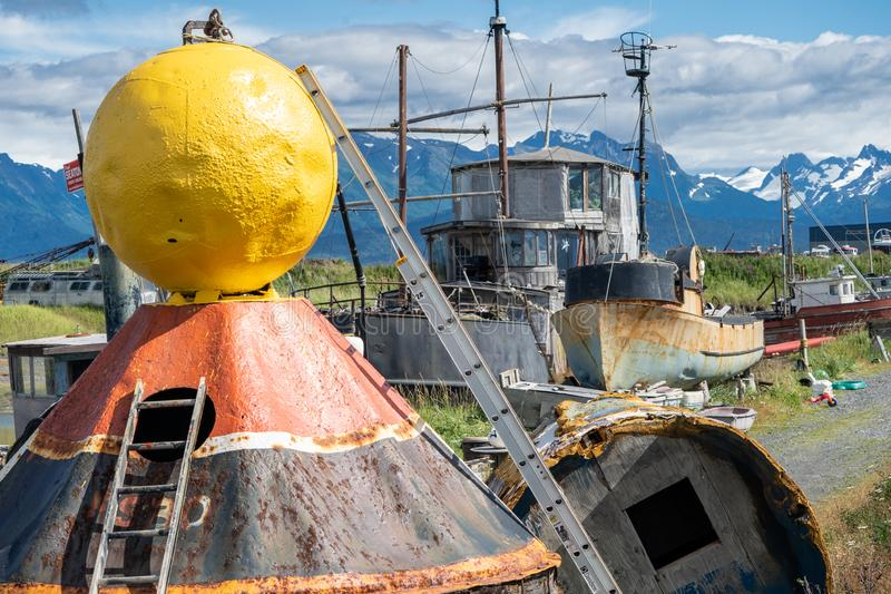 Abandoned boats, ships and other junk in a junkyard in Alaska stock image