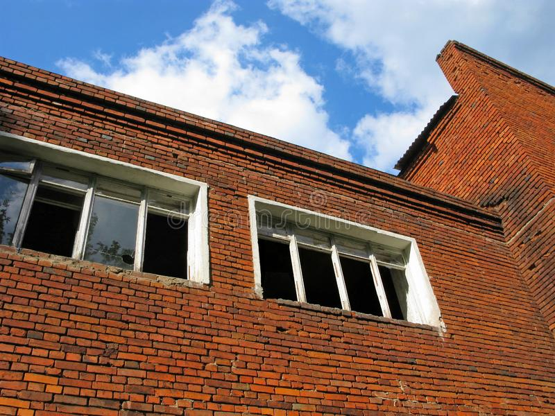 Abandoned brick building, broken and empty windows. Old building in decay. Photo bottom up on the background of blue sky stock photo