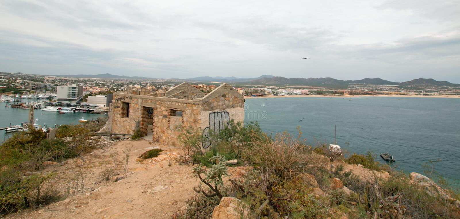 Abandoned brick and stone building on hill above Cabo San Lucas marina and harbor in Baja California Mexico. BCS royalty free stock image