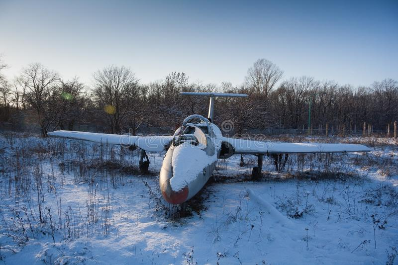 Abandoned broken old military fighter airplane covered with snow stock images