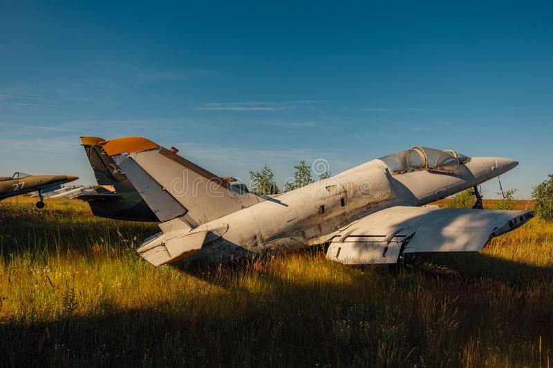 Abandoned broken old Soviet military fighter airplanes on grassy ground. Abandoned broken wrecked old Soviet military fighter airplanes on grassy ground stock photo