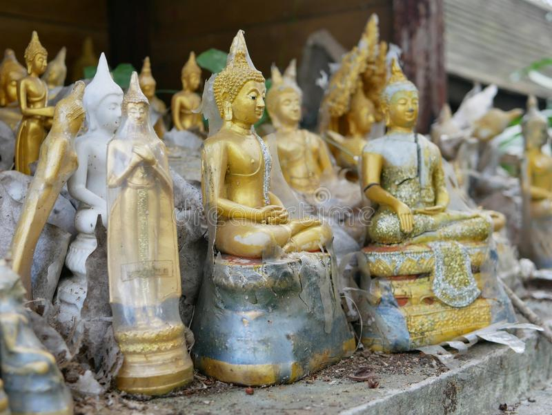 Abandoned Buddha statues / images on old spirit house. Selective focus of abandoned different shapes, styles, and sizes of the Buddha statues / images on old stock photography