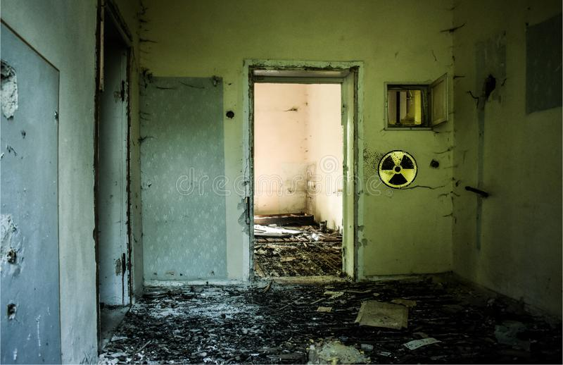 Abandoned building with broken glass and grunge walls because of nuclear accident. Radioative warning sign on the wall. Chernobyl. Pripyat atmosphere stock photo