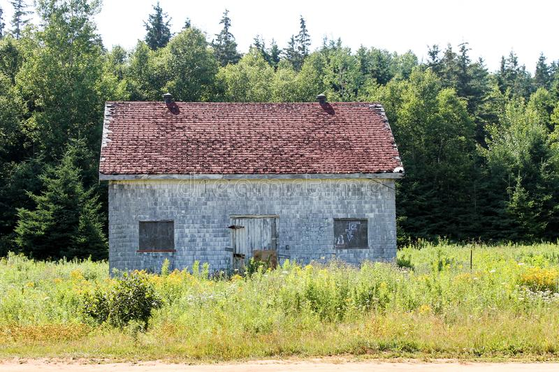 Abandoned Building Near Lighthouse in Prince Edward Island. Small abandoned building in front of forest, overlooking the shores of Prince Edward Island. Located stock photography