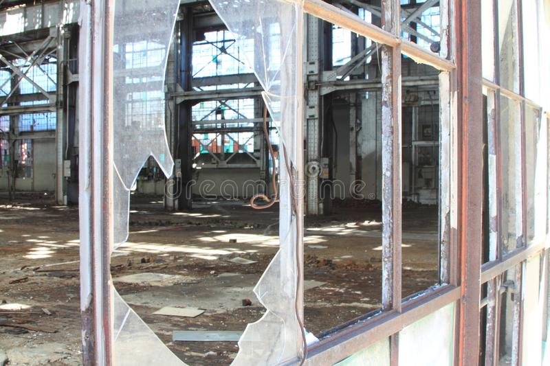 Broken and cracked industrial windows in metal frames royalty free stock photo