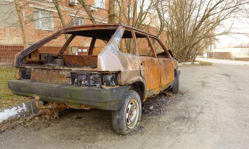 Abandoned burned passenger car near the apartment building. Russia royalty free stock images