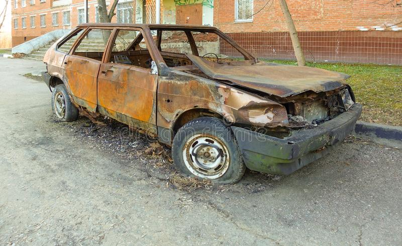 Abandoned burned passenger car near the apartment building. Russia royalty free stock photos