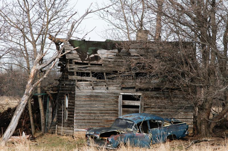 Abandoned cabin and car. Car, cabin, old, delapidated, broken, rusty, home, housr, house, empty, collapse, collapsed, farm, wood, plank, barn, falling, apart royalty free stock photography