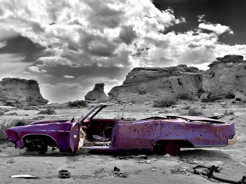 Abandoned car. An abandoned, bullet-hole ridden car, lays rusting away on the outskirts of town