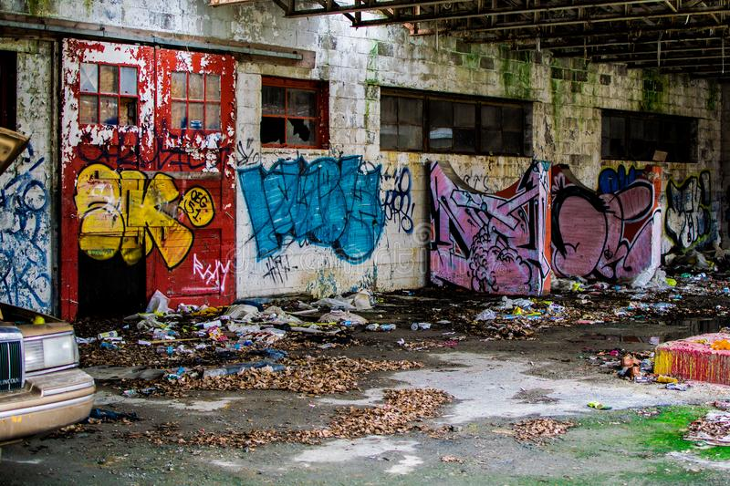 Abandoned car Graffiti building in flint michigan. Abandoned car and graffiti in building in flint Michigan urban decay demolition royalty free stock photo