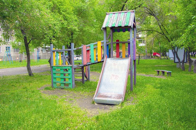 Abandoned children`s playground in the ordinary courtyard of an apartment building royalty free stock photo