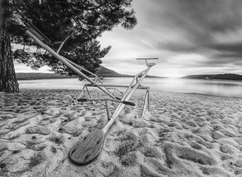 Abandoned children seesaw at lake. Smooth water level. And island at horizon. End of season in natural swimming resort. Black and white photo stock images