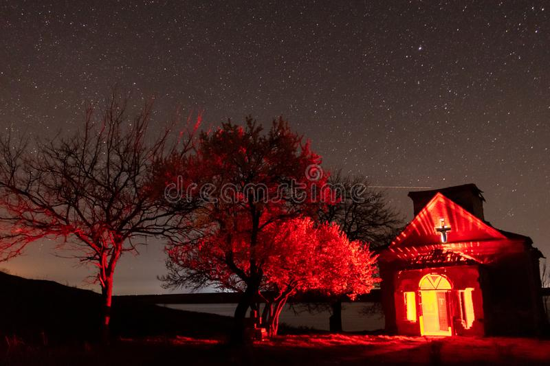 Abandoned church with red light inside and blooming trees nearby nightscape stock photography
