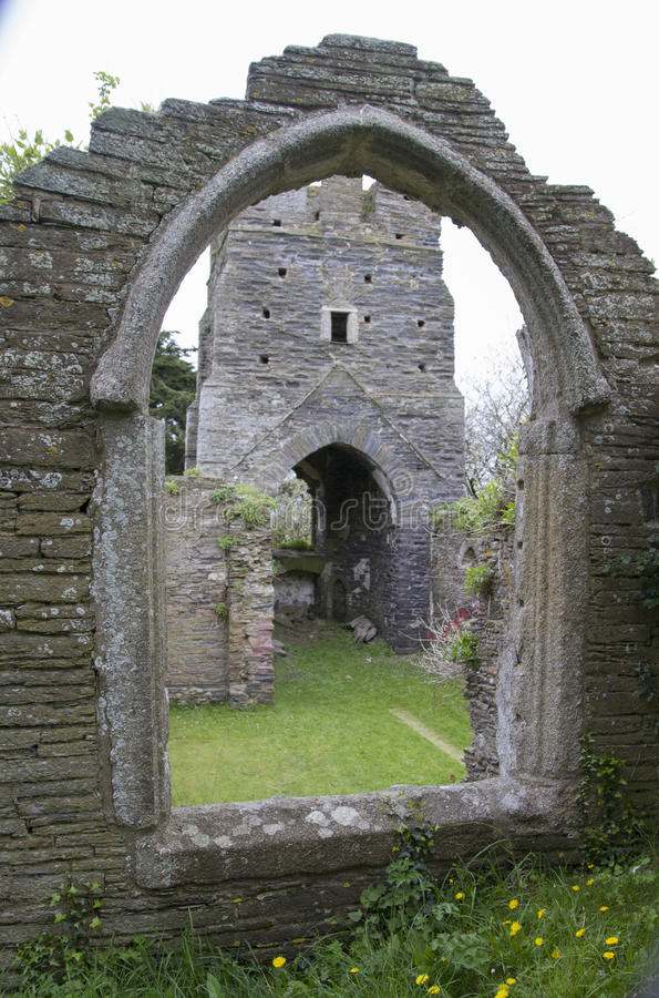 Abandoned church in South Huish, Devon. Stone window framing the ancient tower and entrance royalty free stock images