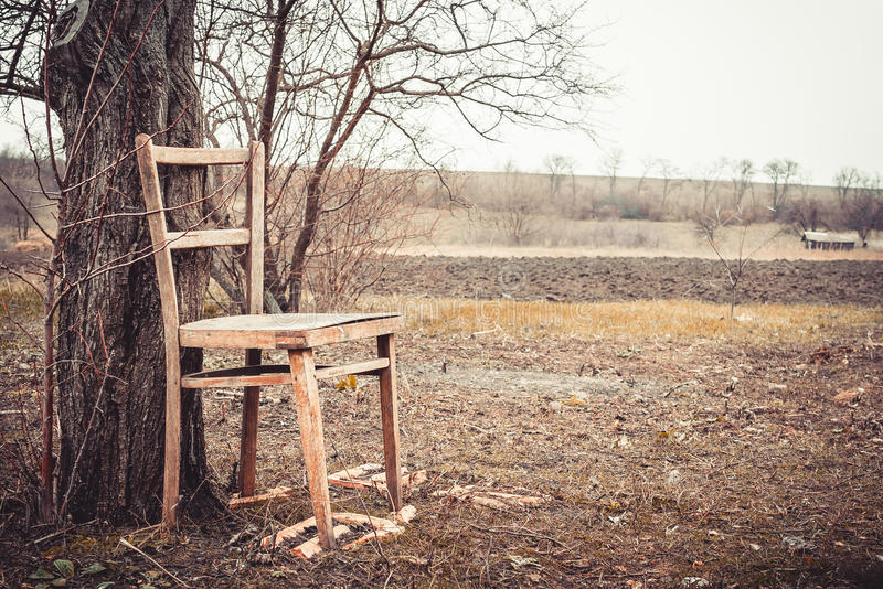 Abandoned country estate. Old age and loneliness. Old broken wooden chair against the dismal garden in early spring. Old age and loneliness. Beauty, simplicity royalty free stock images
