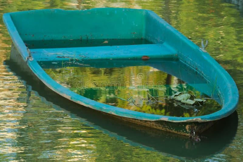 An abandoned, derelict, aqua-blue, fiberglass boat, in a beautiful, reflective garden pond. stock image
