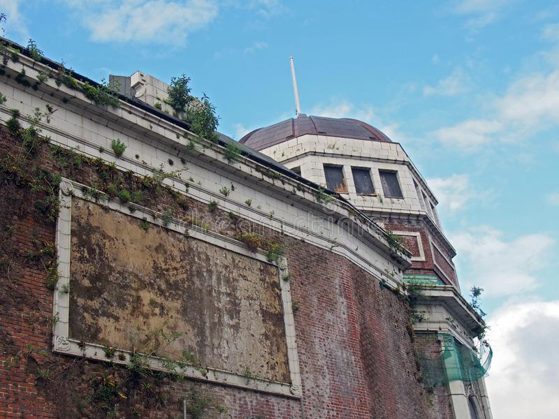 The abandoned derelict historic former odeon cinema in bradford west yorkshire england with decaying walls overgrown with plants. And cracked stonework stock photography