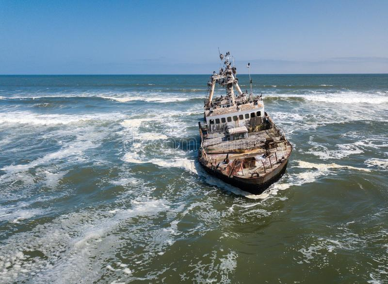 Abandoned and derelict old shipwreck Zeila at the Atlantic Coast near Swakopmund and famous Skeleton Coast in Namibia. Africa. Group of cormorants birds royalty free stock image