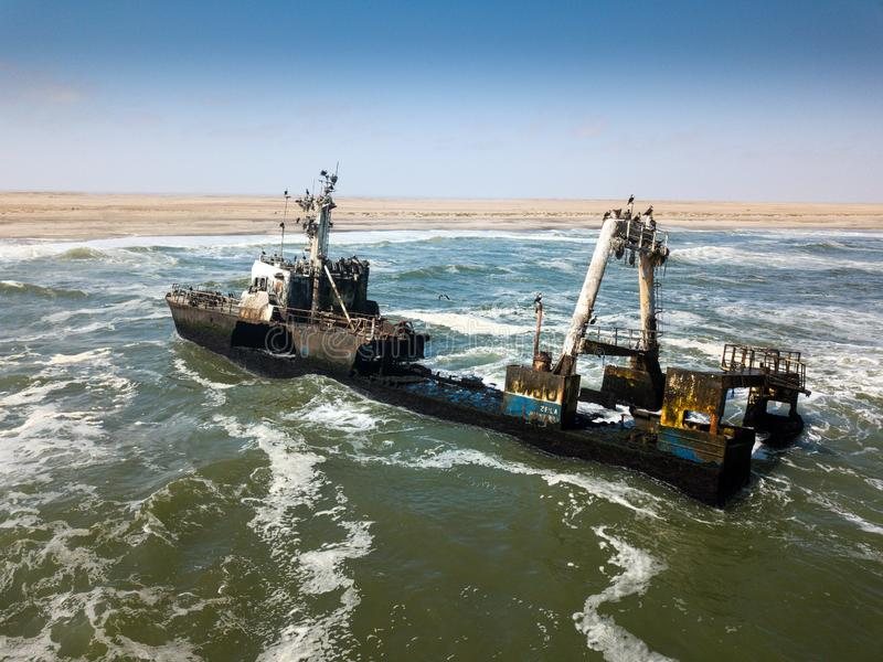 Abandoned and derelict old shipwreck Zeila at the Atlantic Coast near Swakopmund and famous Skeleton Coast in Namibia. Africa. Group of cormorants birds royalty free stock photo