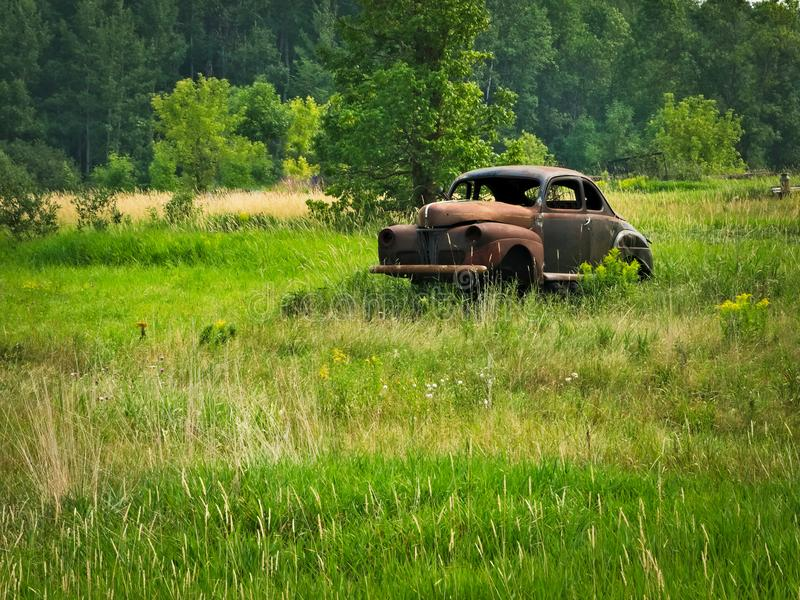 Abandoned deserted rusty old classic car in a farm field stock images