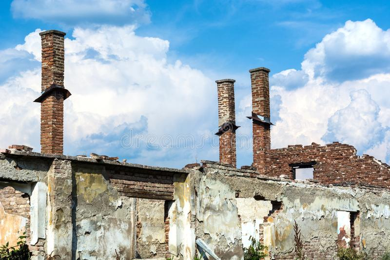 Abandoned destroyed old family brick house without roof and with chimneys stock photography