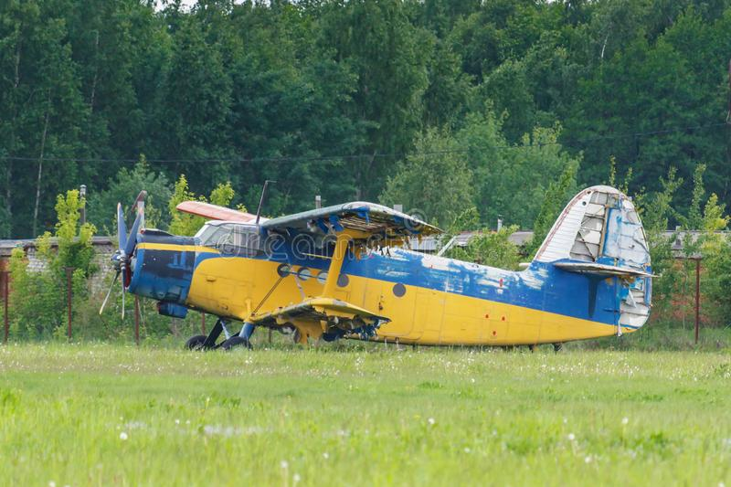 Abandoned and destroyed soviet aircraft biplane Antonov AN-2 parked on a green grass on the edge of the airfield stock images