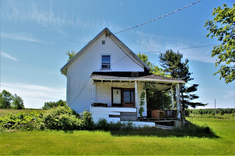 Abandoned dilapidated old house located in Franklin County, upstate New York, United States. Abandoned dilapidated old wooden house with surrounding green royalty free stock image