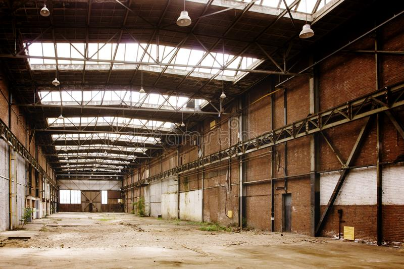 Abandoned empty old factory workshop interior. With roof light stock image