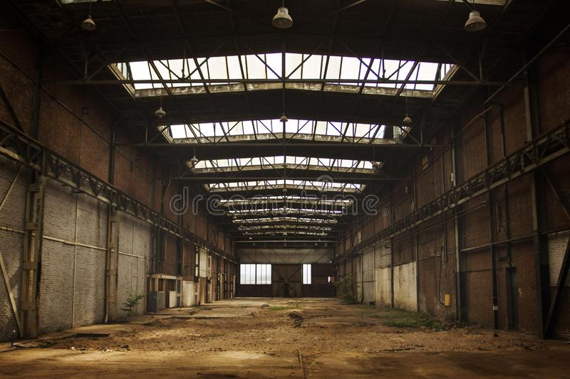 Abandoned empty old factory workshop interior. With roof light stock images