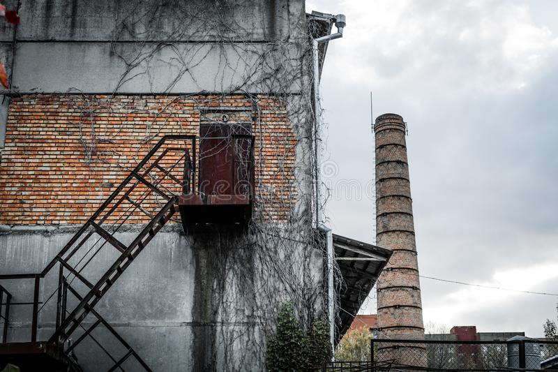Abandoned Factory. Rusty staircase to the factory building and heat pipe stock images