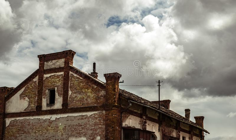 Abandoned factory warehouse with broken windows and plaster fallen. On cloudy sky royalty free stock photography