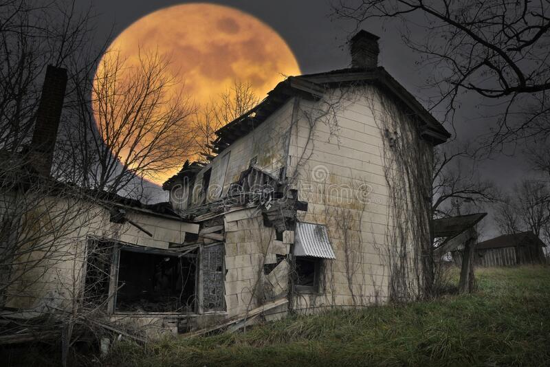 Abandoned farmhouse with a beautiful harvest full moon rising in the background. An abandoned farmhouse with a beautiful harvest full moon rising in the royalty free stock image