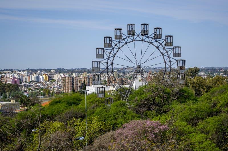 Abandoned Ferris wheel. Decorating the amazing background of Cordoba cityscape taken from Sarmiento park royalty free stock image