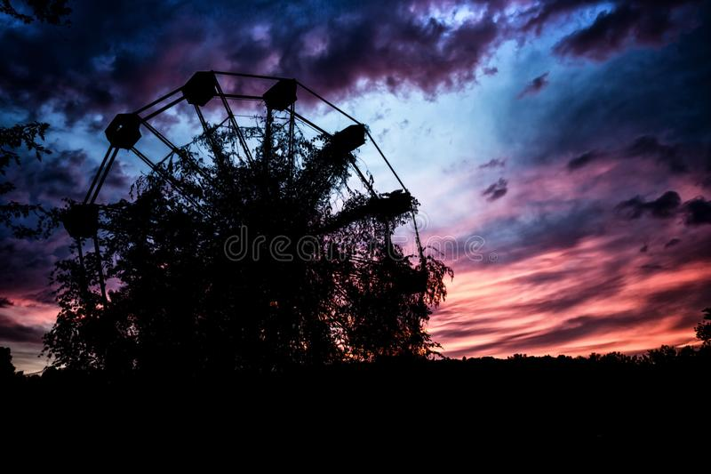 Ominous Abandoned Ferris Wheel. An abandoned ferris wheel sits against the dark sunset royalty free stock photo